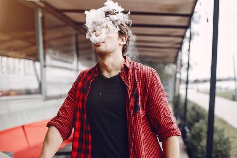 E sigara kullanan adam