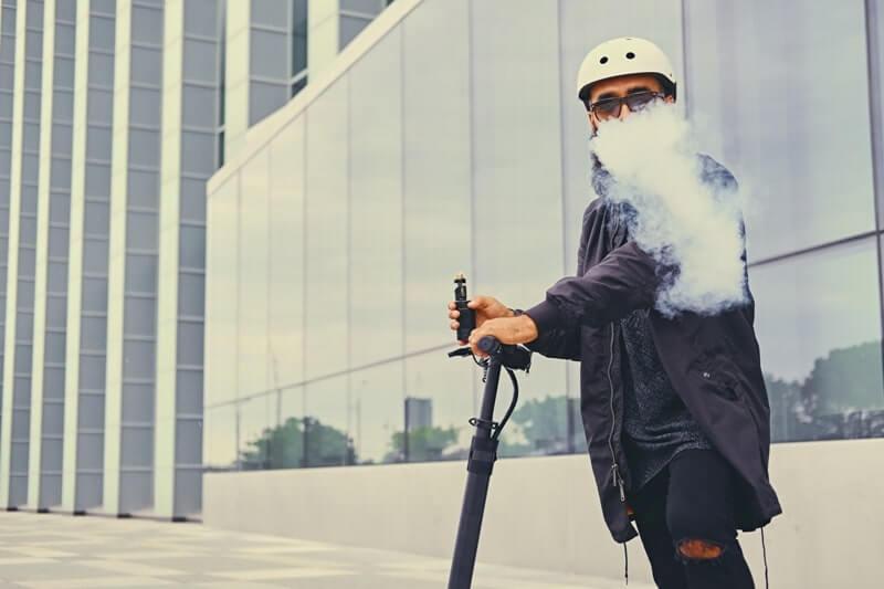 Scooter üzerinde e sigara içen bir adam